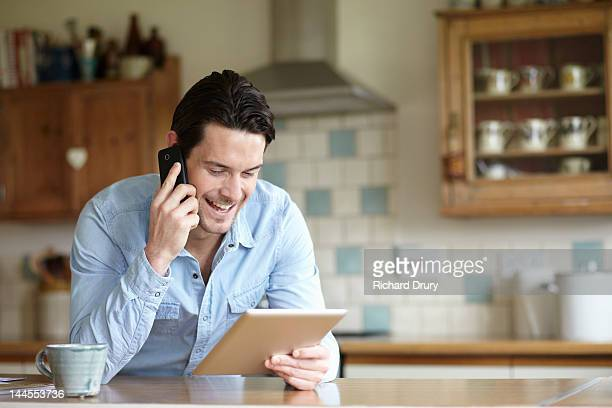 Man using digital tablet and phone in kitchen