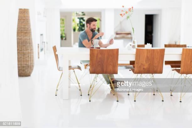 Man using digital tablet at breakfast table in modern dining room
