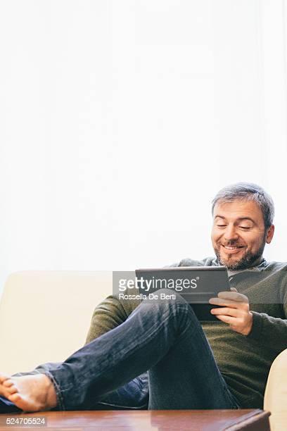 Homem usando Tablet Digital em Casa