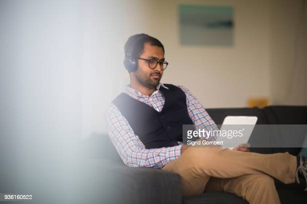 man using digital tablet at home - sigrid gombert stock pictures, royalty-free photos & images