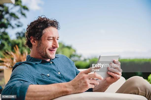 Man using digital tablet at yard