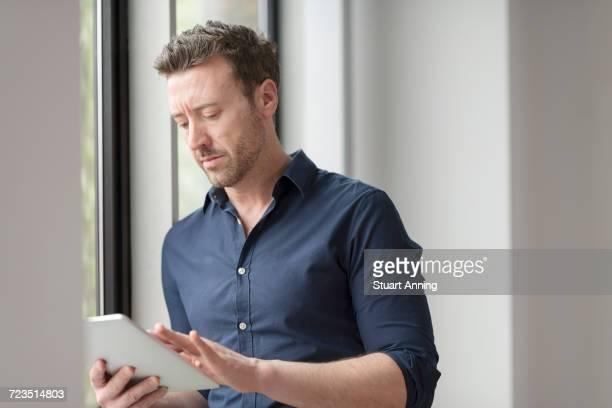 Man using digital tablet by office window