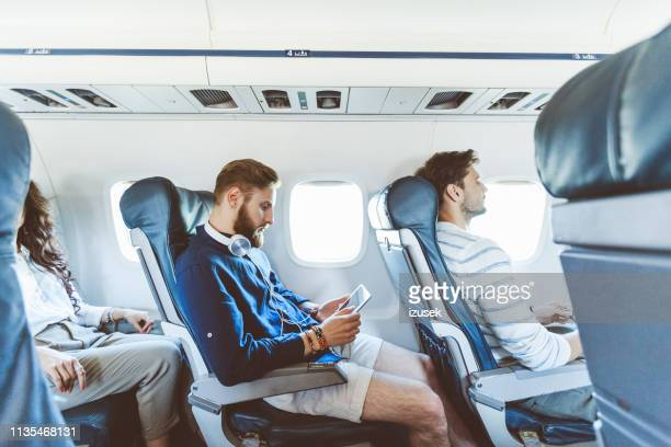 man using digital tablet during his journey by airplane - passengers 2016 film stock pictures, royalty-free photos & images