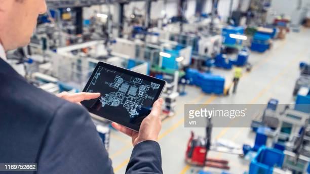 工場でデジタルタブレットを使用している男性 - 見渡す ストックフォトと画像