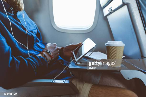 man using digital tablet in airplane - passengers 2016 film stock pictures, royalty-free photos & images