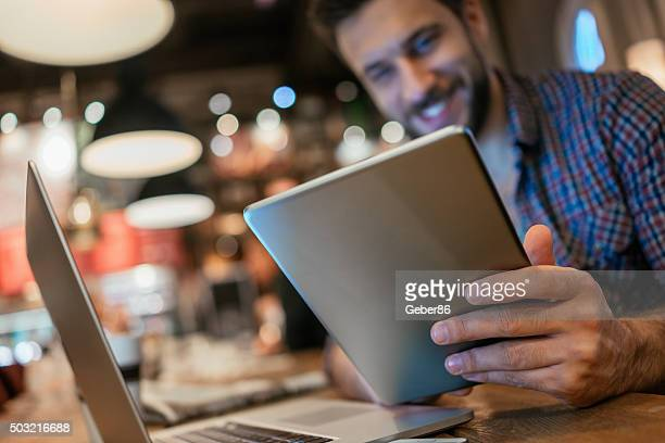 Man using digital tablet in cafe