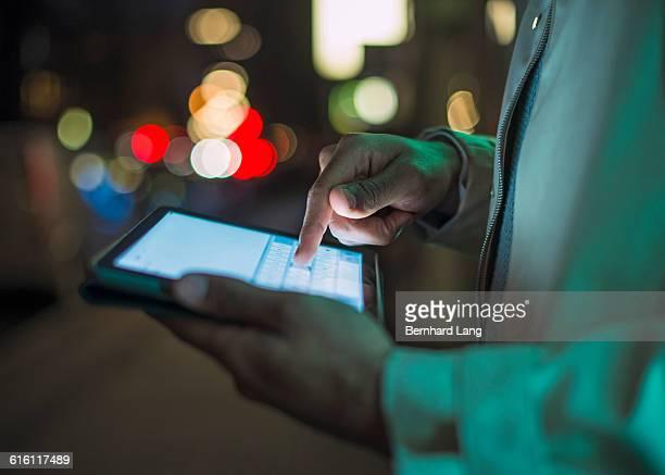 Man using digital tablet in city, close up