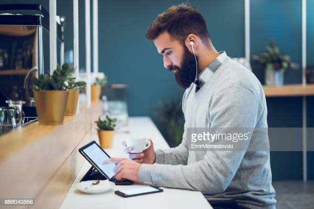 man using digital tablet in coffee bar - blogging stock pictures, royalty-free photos & images