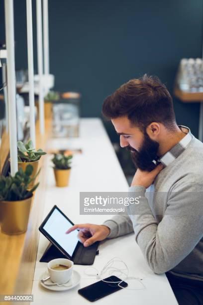 Hombre usando tableta digital en barra de café
