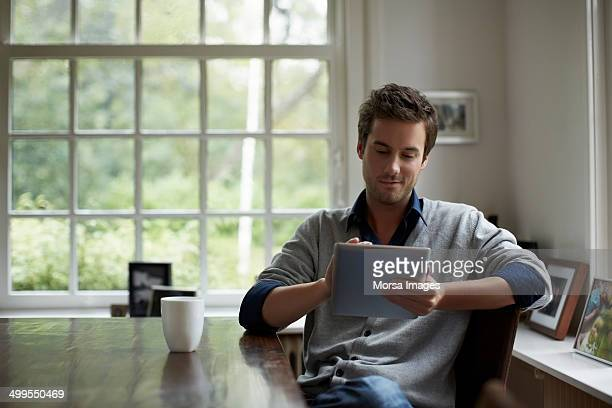 man using digital tablet in cottage - tablet benutzen stock-fotos und bilder