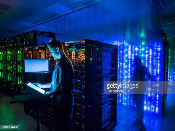 Man using digital tablet in dark server room