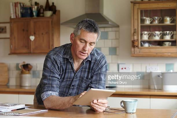 man using digital tablet in kitchen - rolled up sleeves fotografías e imágenes de stock
