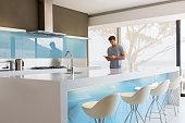 Man using digital tablet in modern kitchen