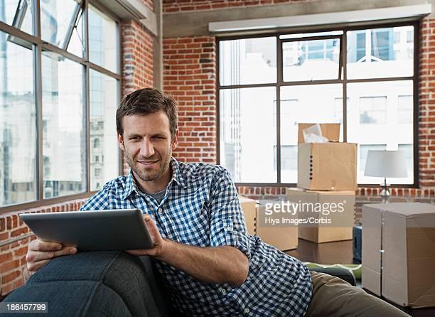 Man using digital tablet in new apartment
