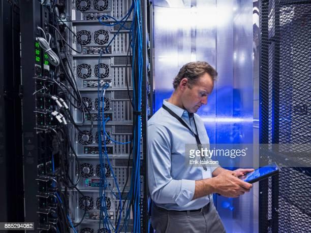 Man using digital tablet in server room