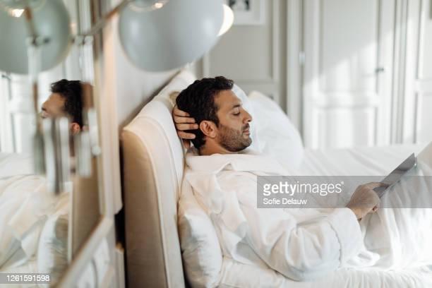 man using digital tablet in suite - florence douillet photos et images de collection