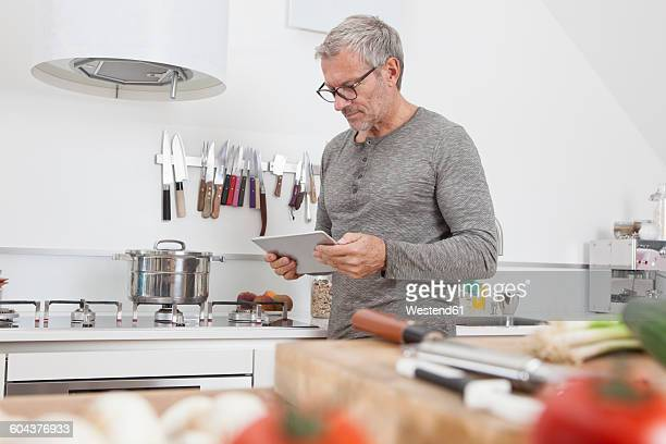 Man using digital tablet in the kitchen