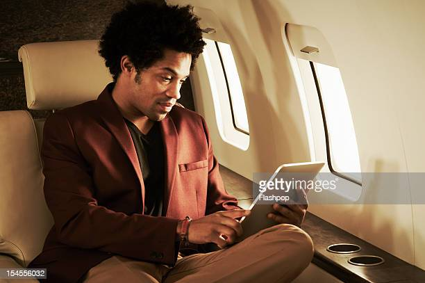 Man using digital tablet on private jet