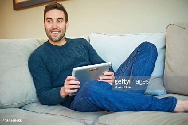 man using digital tablet on sofa - 僅一男人 個照片及圖片檔