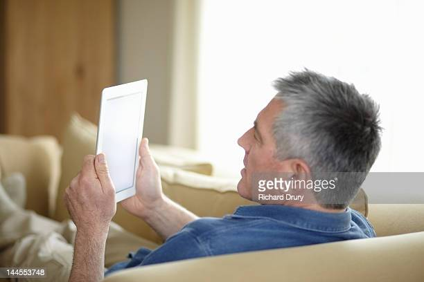 man using digital tablet on sofa - richard drury stock pictures, royalty-free photos & images