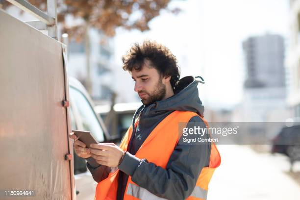 man using digital tablet on street - sigrid gombert stockfoto's en -beelden