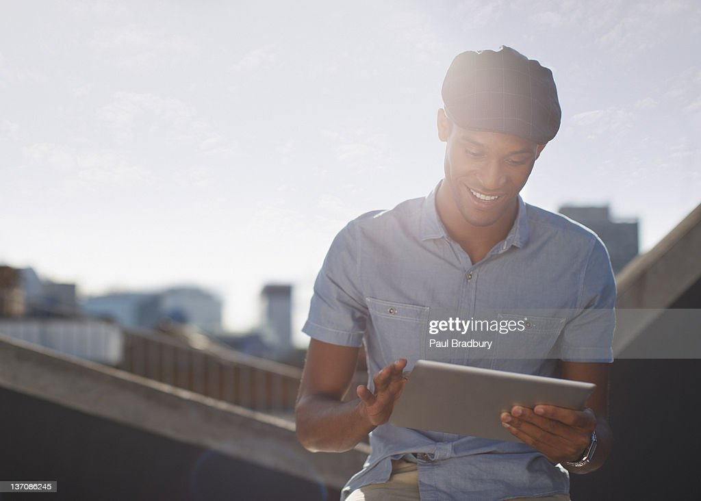 Homme à l'aide de tablette numérique sur sunny bar urbain sur le toit : Photo