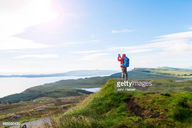 Man using digital tablet to take photo of scenery in mountains.