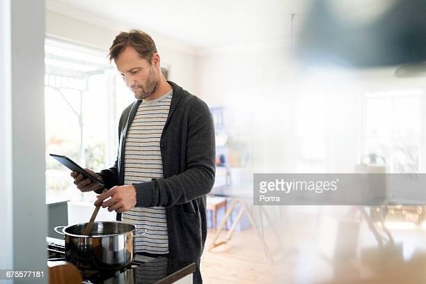 man using digital tablet while cooking in kitchen - ein mann allein stock-fotos und bilder