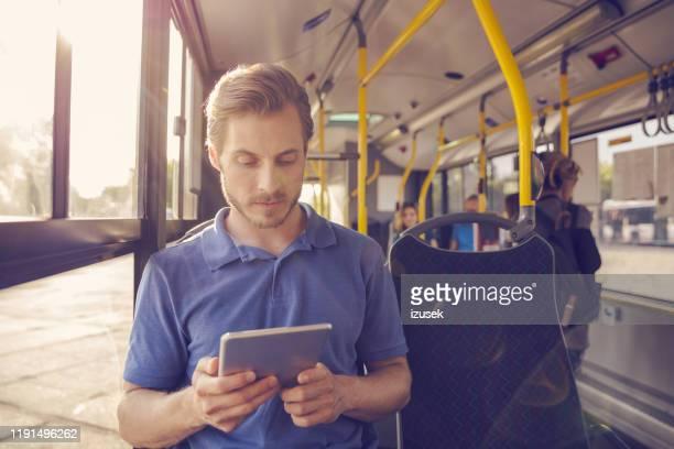 man die digitale tablet gebruikt tijdens het reizen in de bus - izusek stockfoto's en -beelden