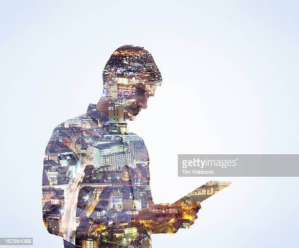 man using digital tablet with city view at night. - data stream stock photos and pictures
