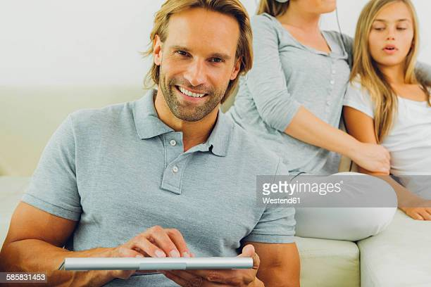 Man using digital tablet with woman and girl in background