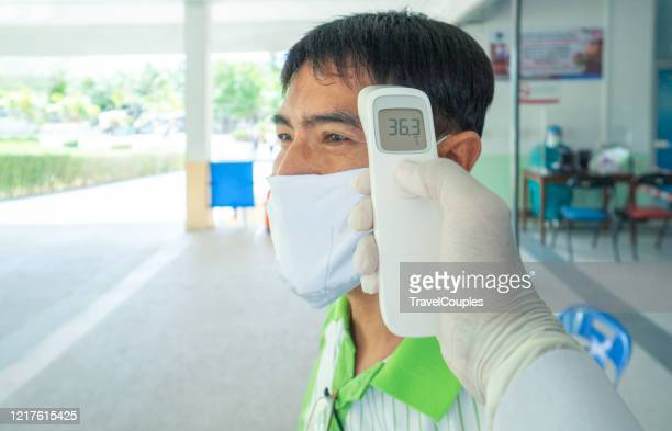 man using digital thermometer isolated on white background, digital infrared thermometer. coronavirus 2019-ncov epidemic outbreak. covid-19 checkpoint. - temperature checkpoint stock pictures, royalty-free photos & images