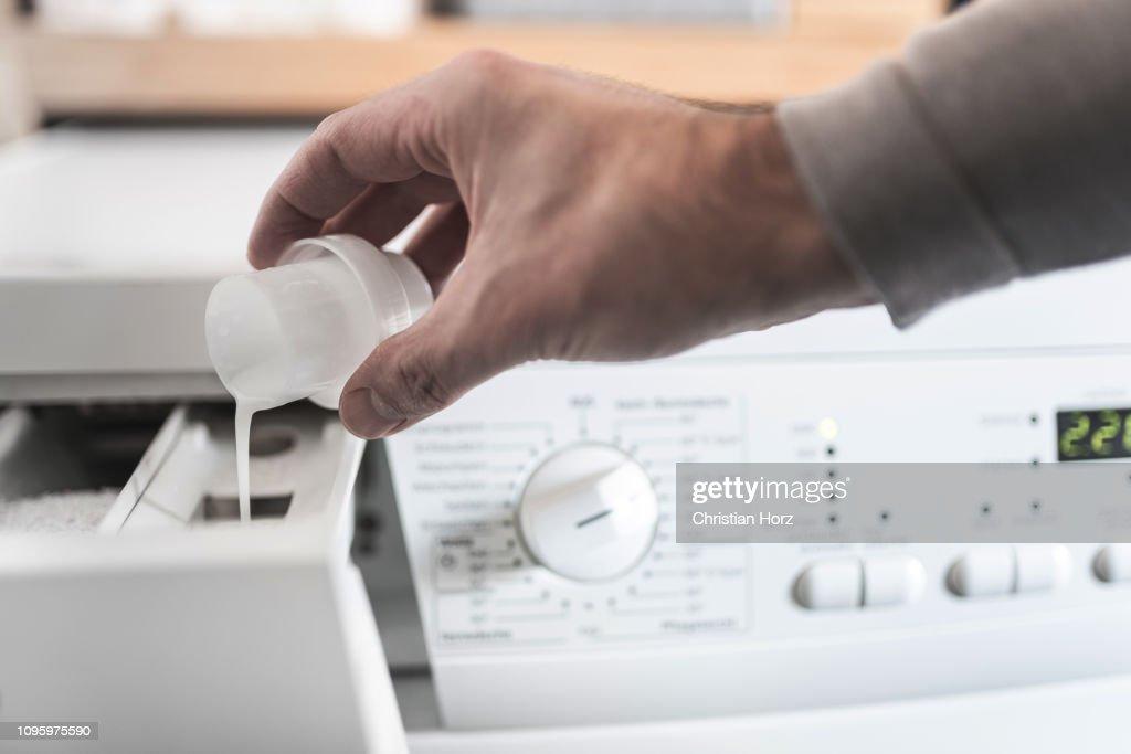 Mann mit Dosierhilfe, Weichspüler in die Waschmaschine zu füllen : Stock-Foto