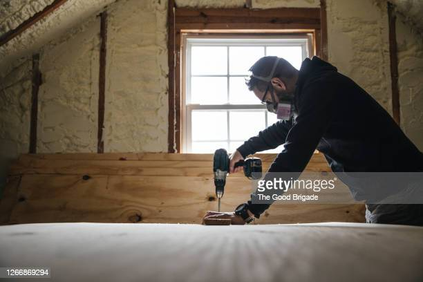 man using drill while renovating attic - effort stock pictures, royalty-free photos & images