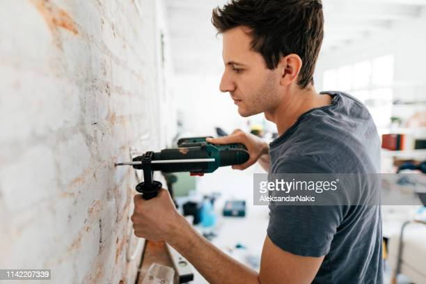 man using drilling machine during reconstruction of his apartment - drill stock pictures, royalty-free photos & images