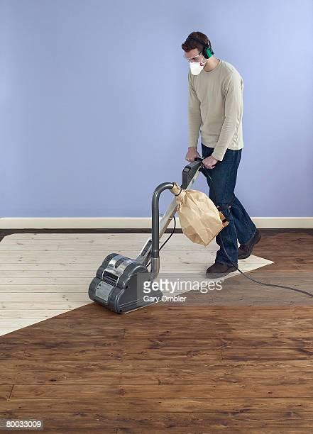 Man using drum sander on partially sanded floor