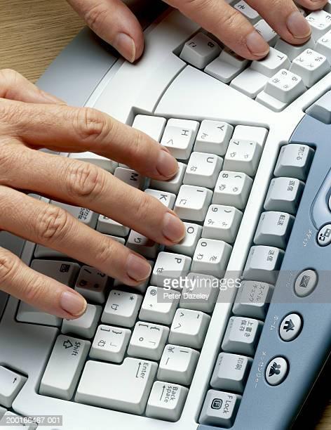 Man using dual language ergonomic keyboard, close-up