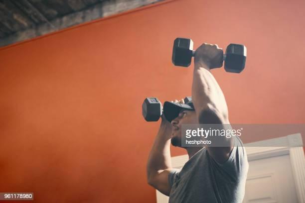man using dumbbells in gym - heshphoto stock-fotos und bilder
