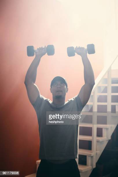 man using dumbbells in gym - heshphoto stock pictures, royalty-free photos & images