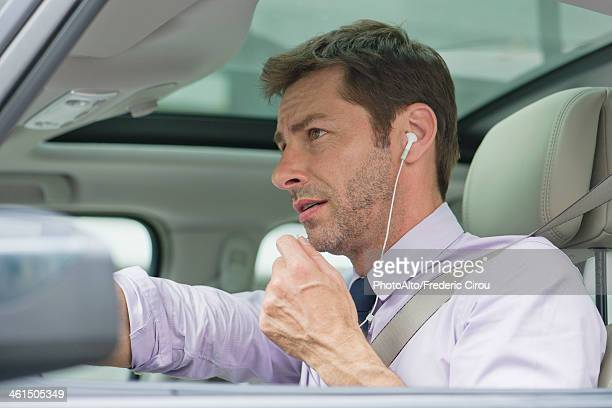 Man using earphone headset while driving