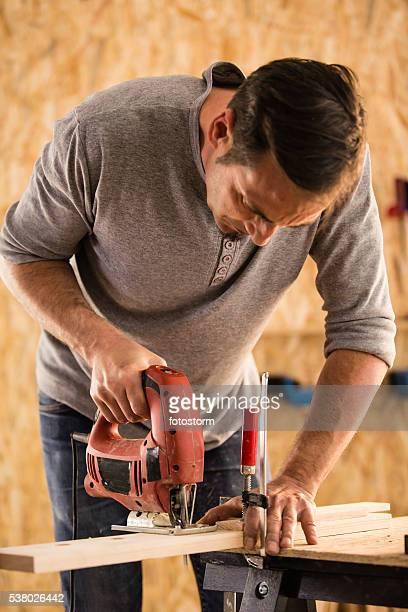 Mann, die elektrische Stichsäge