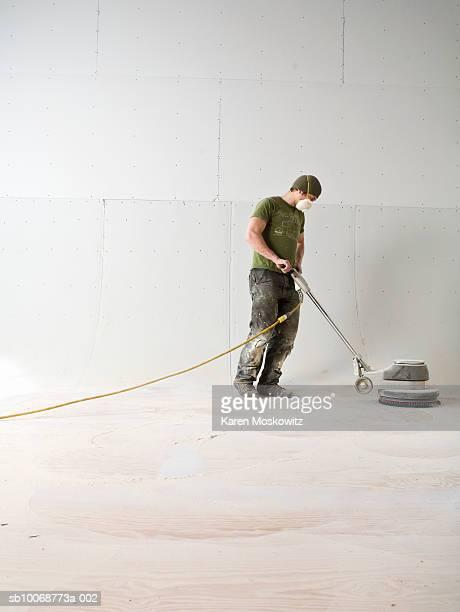 Man using electric sanding floor