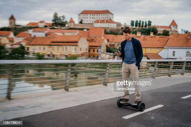 man using electric scooter - hoverboard stock pictures, royalty-free photos & images