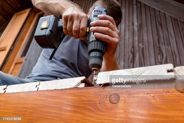 mann mit elektro-screw-bohrer zur fixierung von holzplanen auf new house balcony - kieferngewächse stock-fotos und bilder