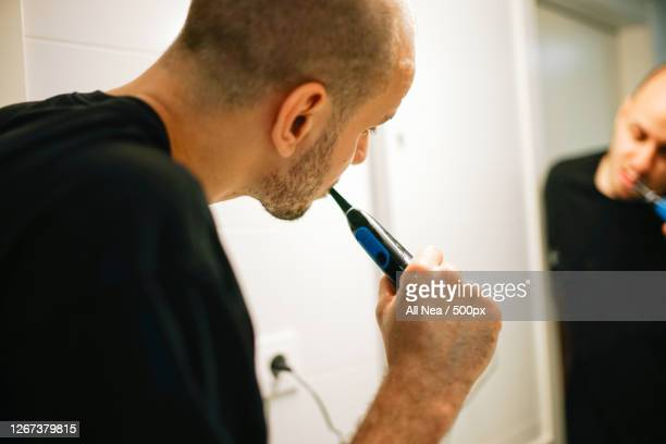 man using electric toothbrush at home, lleida, spain - electric toothbrush stock pictures, royalty-free photos & images