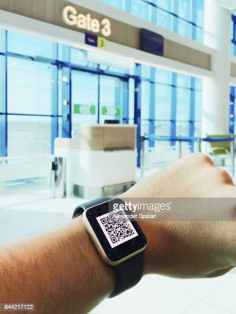 Man using electronic boarding pass on his smart watch near the gate at the airport