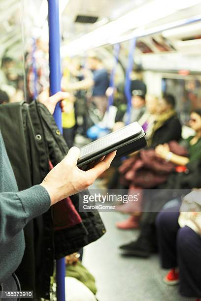 Man using E-Reader on Underground Train