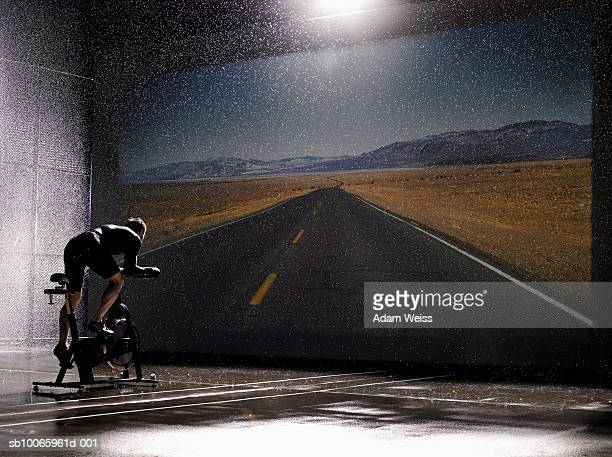 Man using exercise bike in front of road on screen, rear view