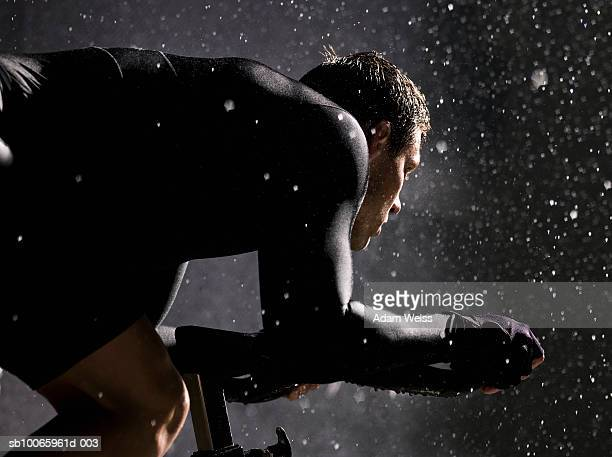 Man using exercise bike in rain at night, side view