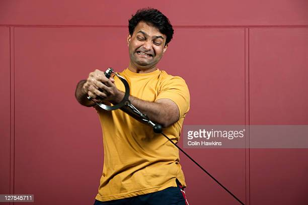 man using exercise machine in gym - struggle stock pictures, royalty-free photos & images